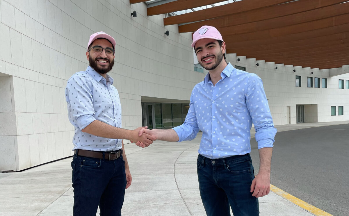 2 Ryserson students saking hands since creating an app for vaccine booking
