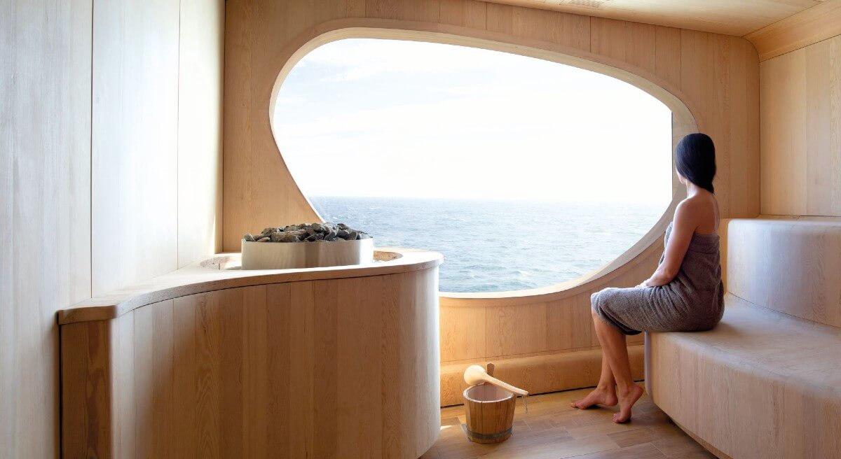woman in towel viewing the ocean from the spa inside the Le Champlain & Le Laperouse (Ponant) Exploration Cruise Ship
