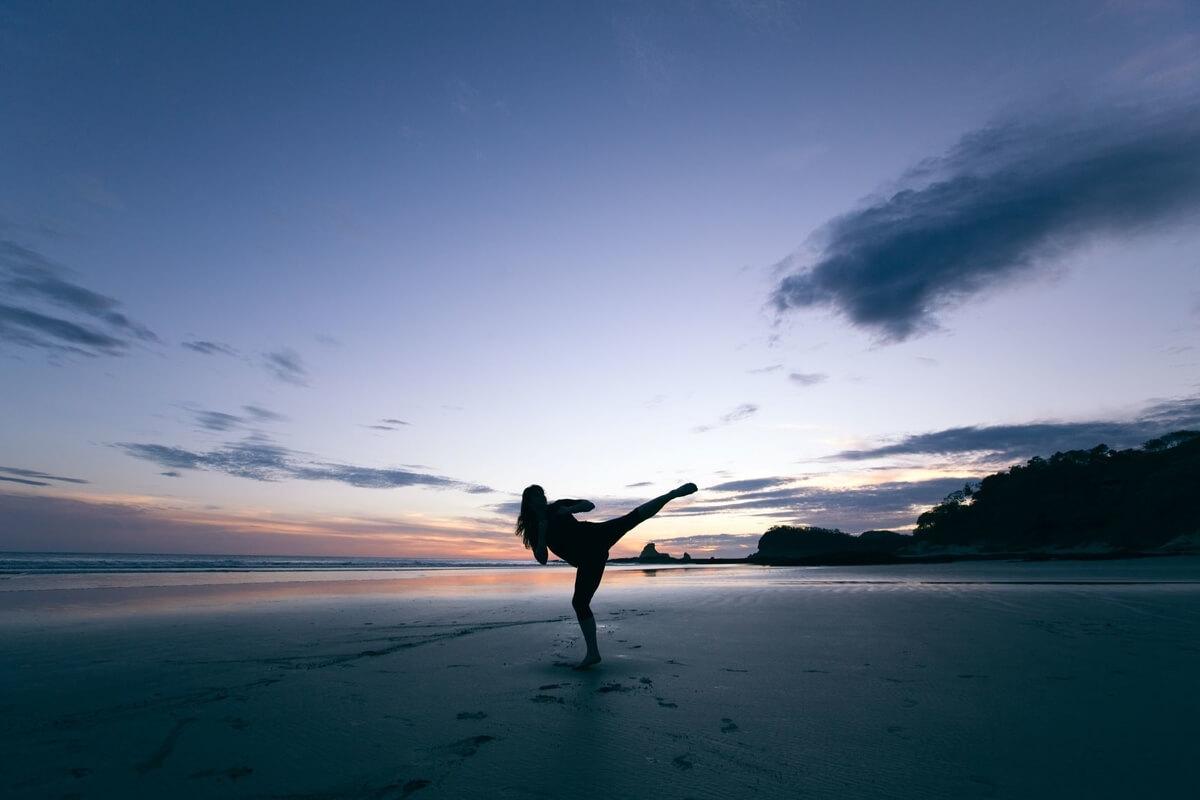 woman kicking on a beach at sunset in a women's self-defense BJJ class