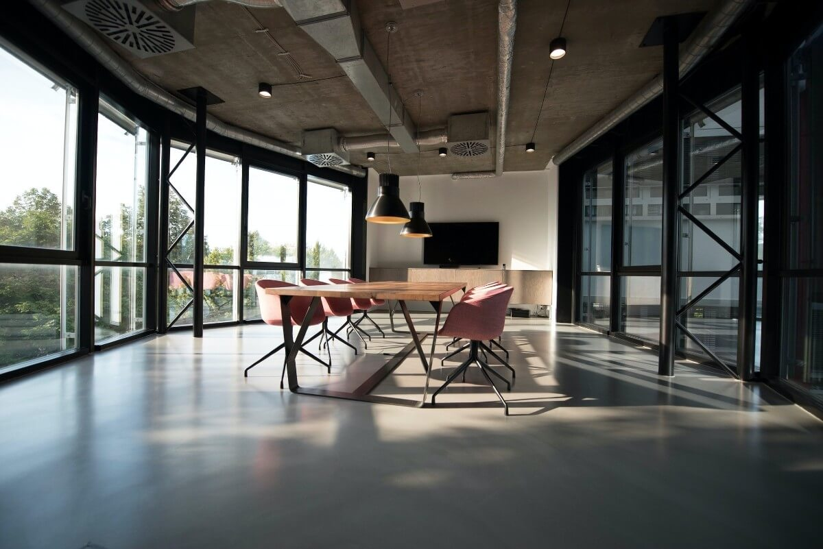 meeting table and chairs in large meeting space with many windows