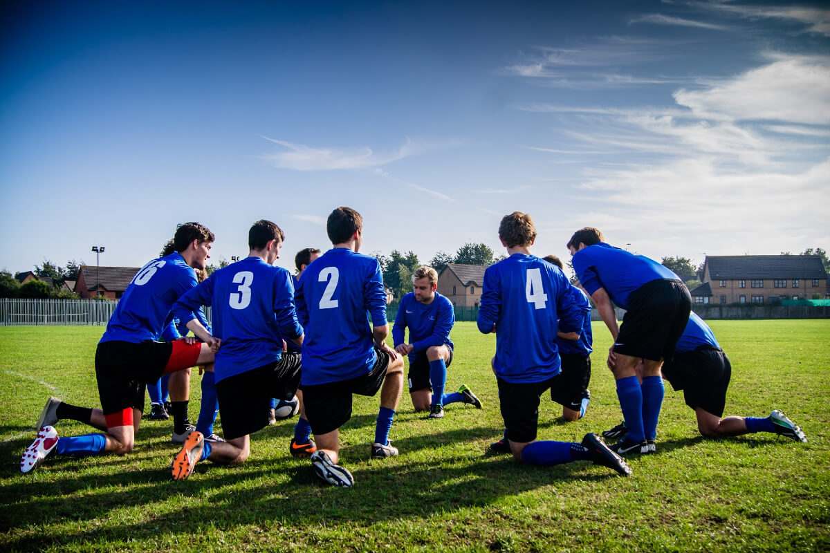 soccer players kneel in circle on pitch, athletes in COVID