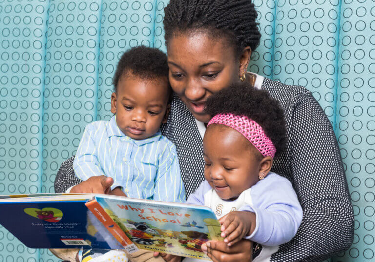 mother and 2 children reading thanks to Dolly Parton Imagination Library