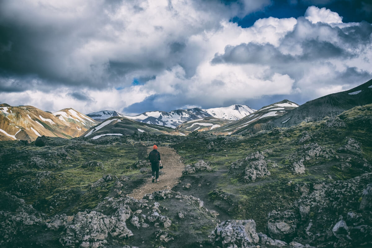 person hiking in the mountains as a way of green travel