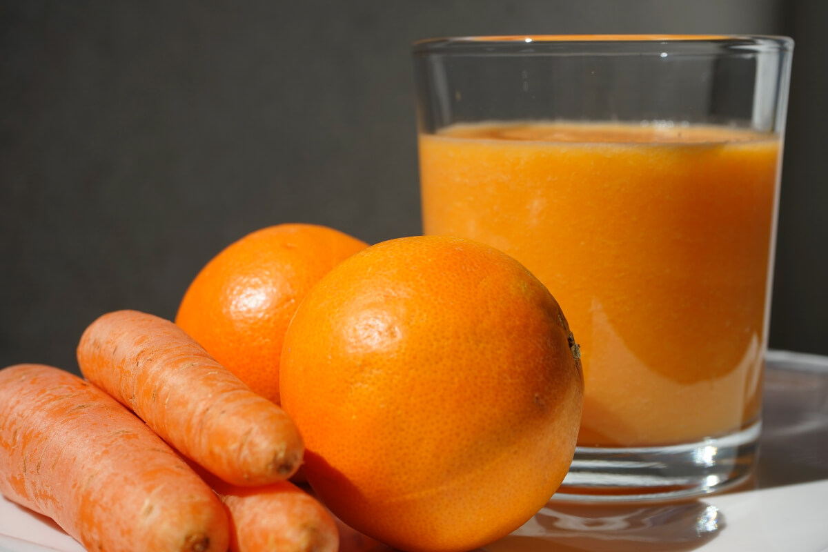 glass of juice, oranges, carrots for juicer recipes