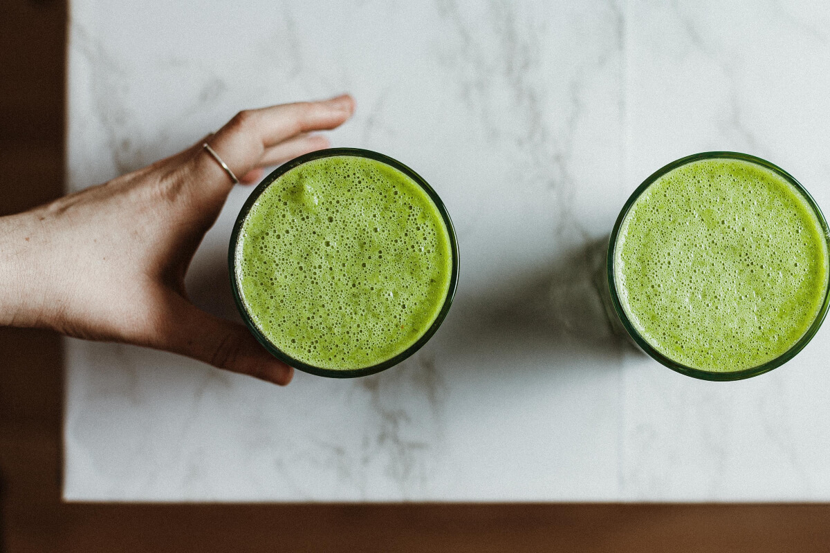 a hand grabbing one of two glasses of green juice