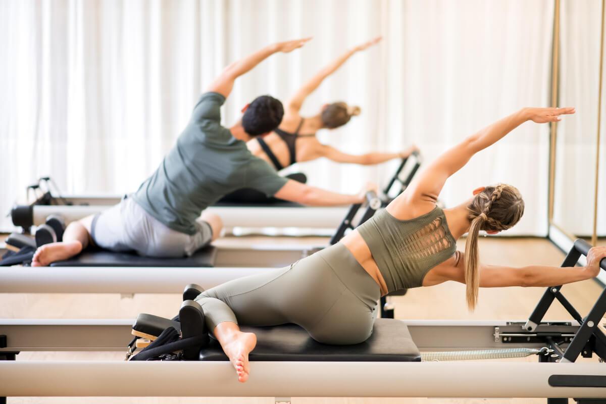 a class of women practicing reformer pilates