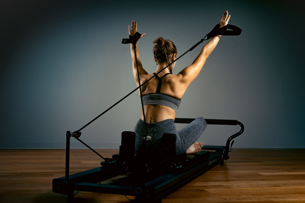 a woman on a machine practicing reformer pilates