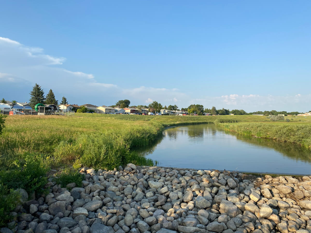 a creek, grass and homes near the The Devonian Pathway in Regina