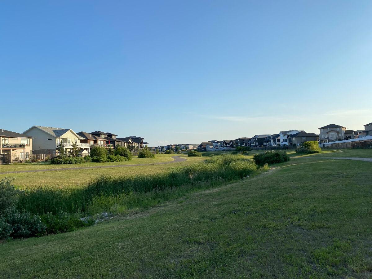 a Regina walking path beside a creek and homes