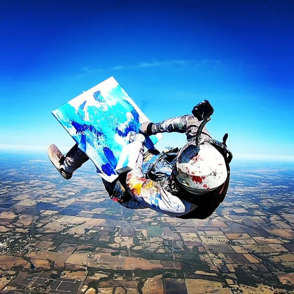 woman skydiving and painting blue colours on canvass