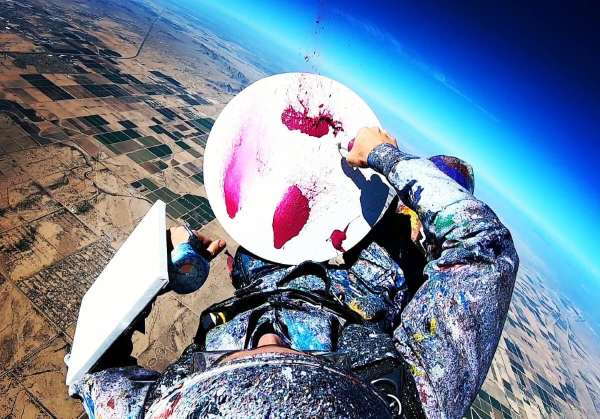 woman skydiving and painting red colours on canvass