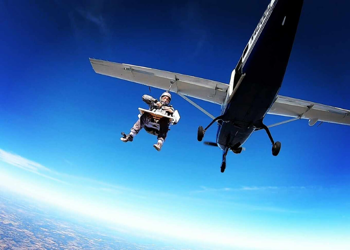 woman supsended from plane before skydiving & painting