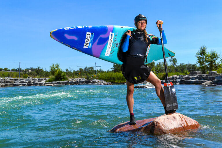 Haley Daniels standing with kayak on her back, ready for the Tokyo Olympics