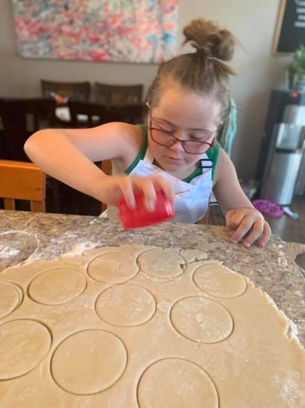 young girl cutting cookies in rolled dough for 21treats