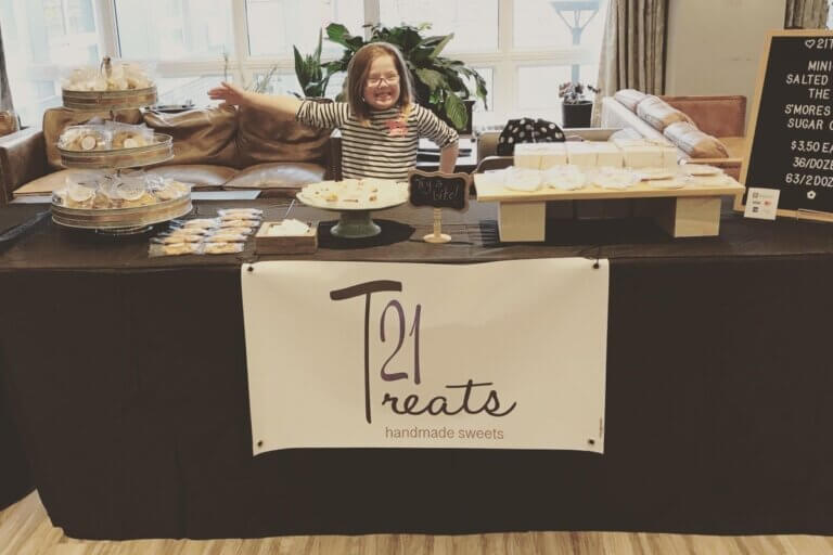 girl standing behind a 21Treats table of cookies