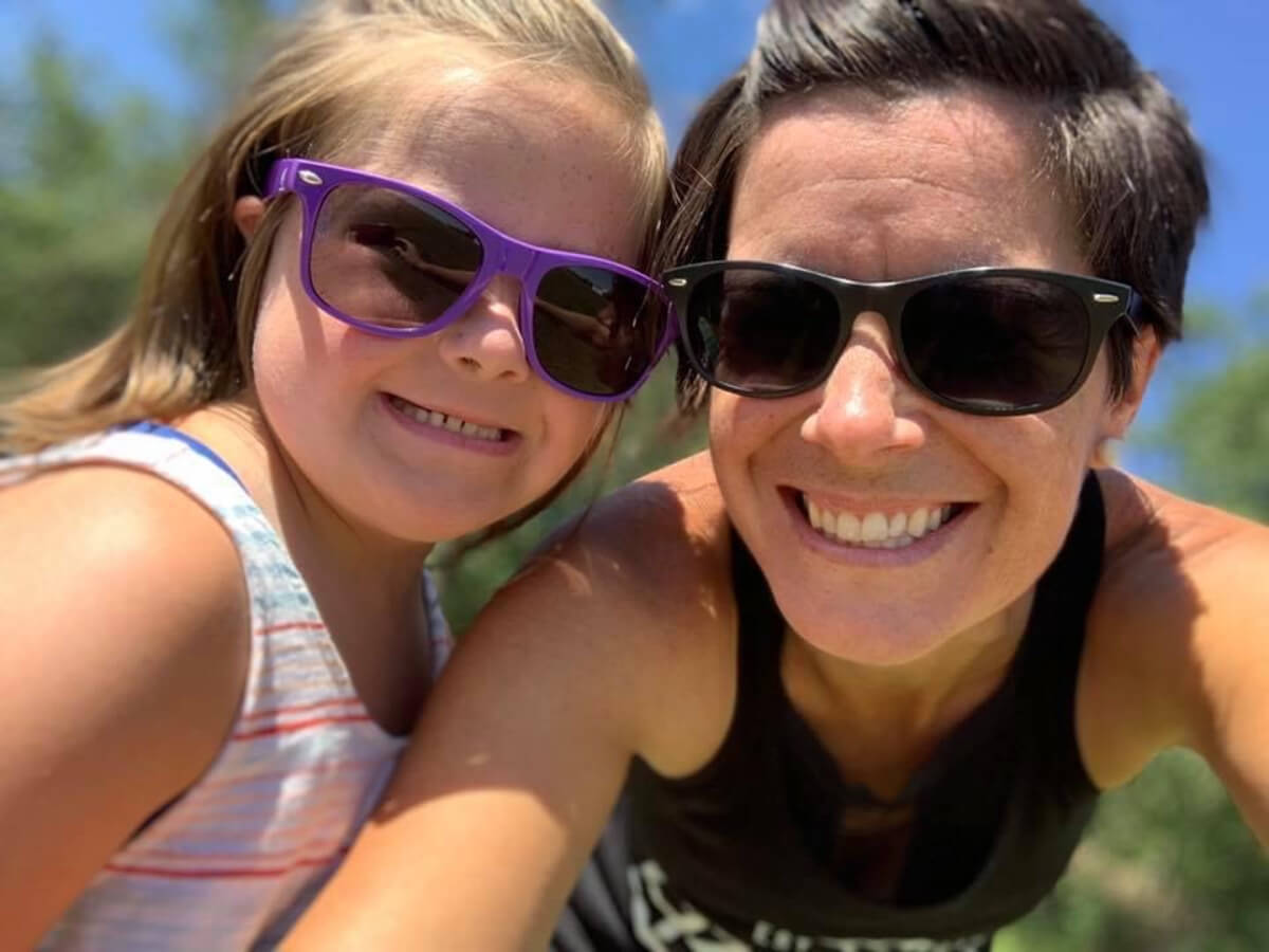 Woman and young girl wearing sunglasses and smiling at camera