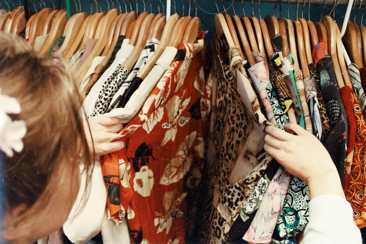 a woman checking recycled clothing on hangers