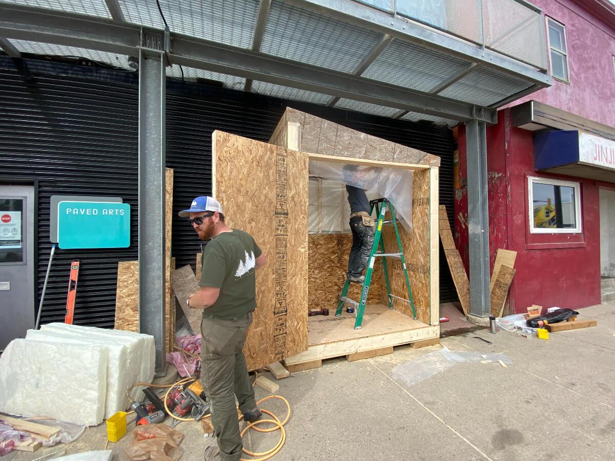 two workers constructing Saskatoon's community fridge