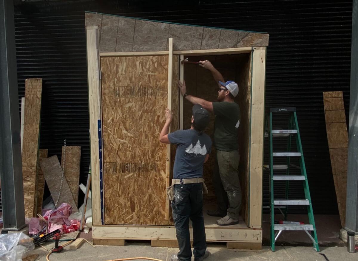 two men building Saskatoon's community fridge