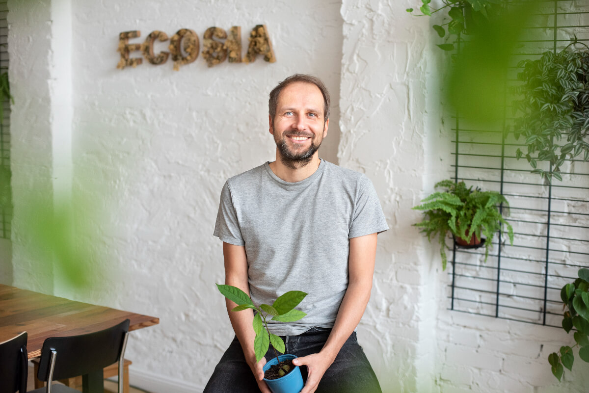 CEO of Ecosia, Christian Kroll, sitting and surrounded by plants in a white room