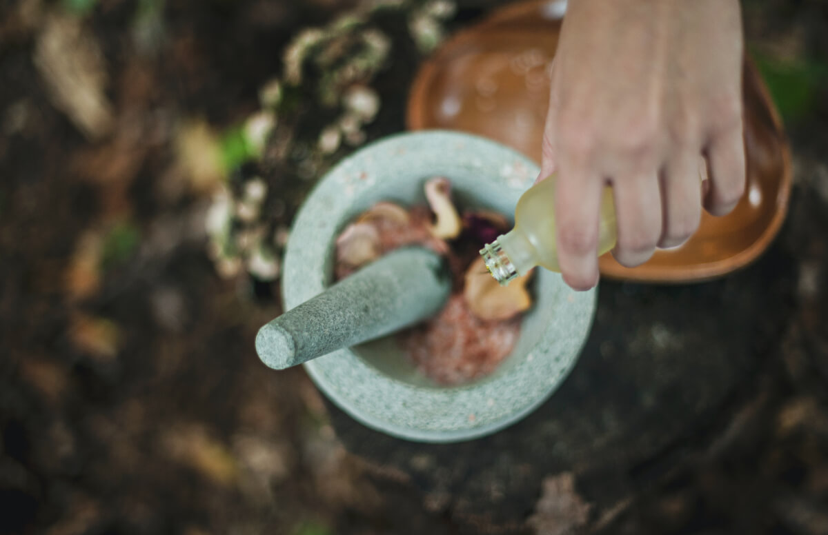 mixing green beauty products in a grey mortar and pestle
