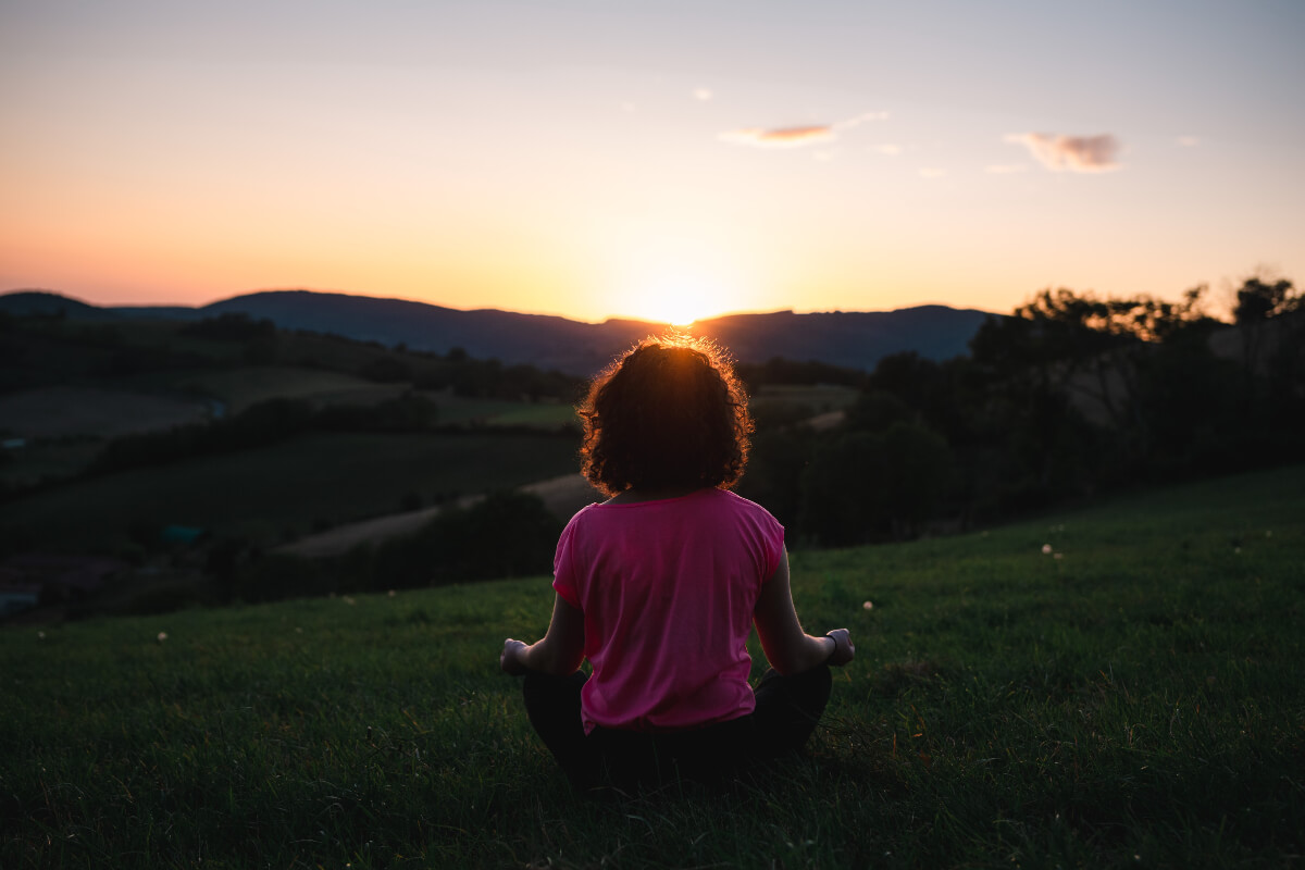 woman meditating outside at sunset for mental wellness