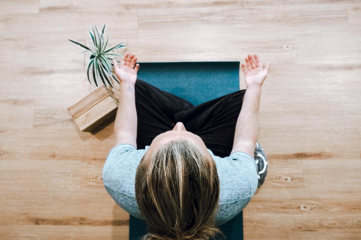 a woman meditating for mental wellness