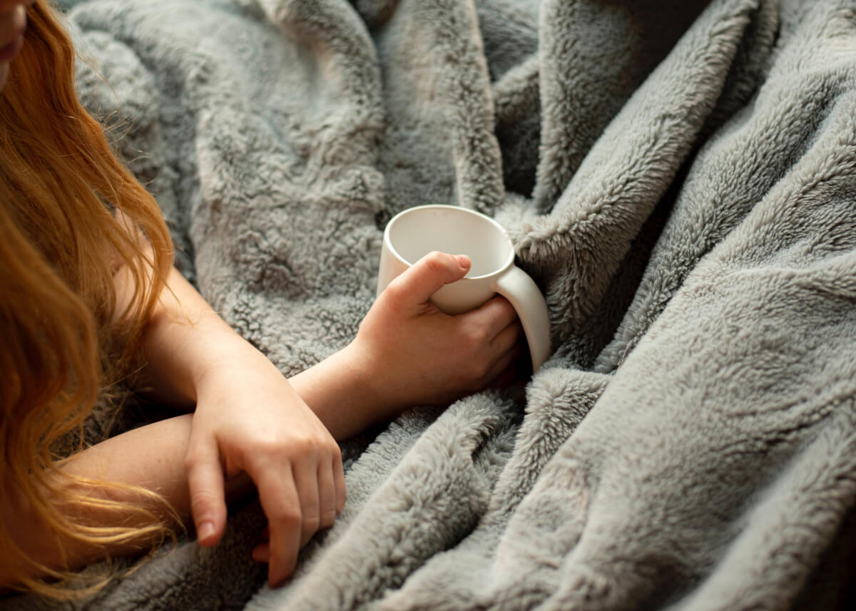 person with long red hair holding a white mug under a weighted blanket, one of many natural anxiety remedies