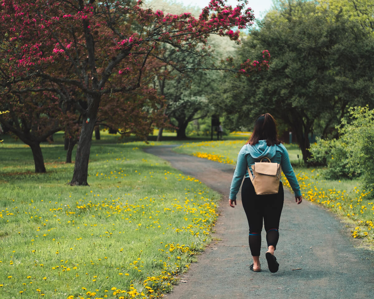 woman walking on trail among trees to elevate her step count
