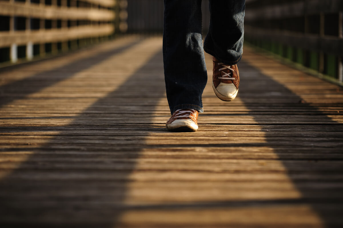 feet and lower legs of a person walking on a bridge