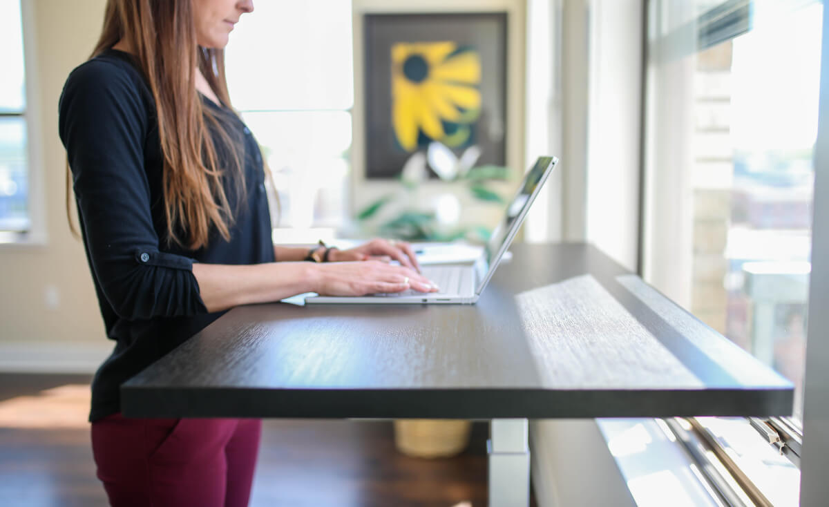 woman working on laptop at standing desk in a bright office