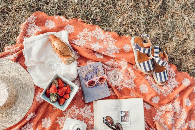 orange blanket with fruit, glasses, sandals and summer 2021 books