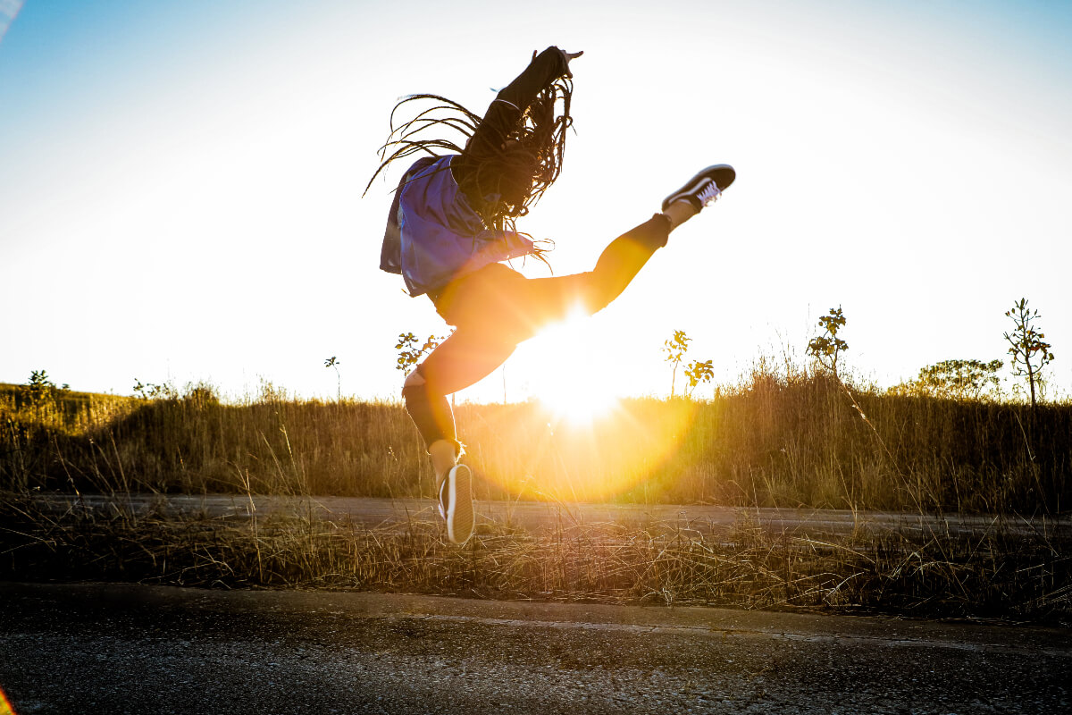 young woman jumping above the ground at sunset, feeling great as a weekday vegan