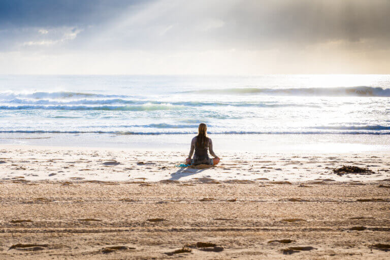 person by the ocean listening to wellness podcasts
