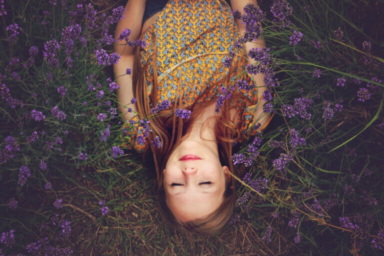 Woman in a yellow floral dress laying in a field of lavender with her eyes closed