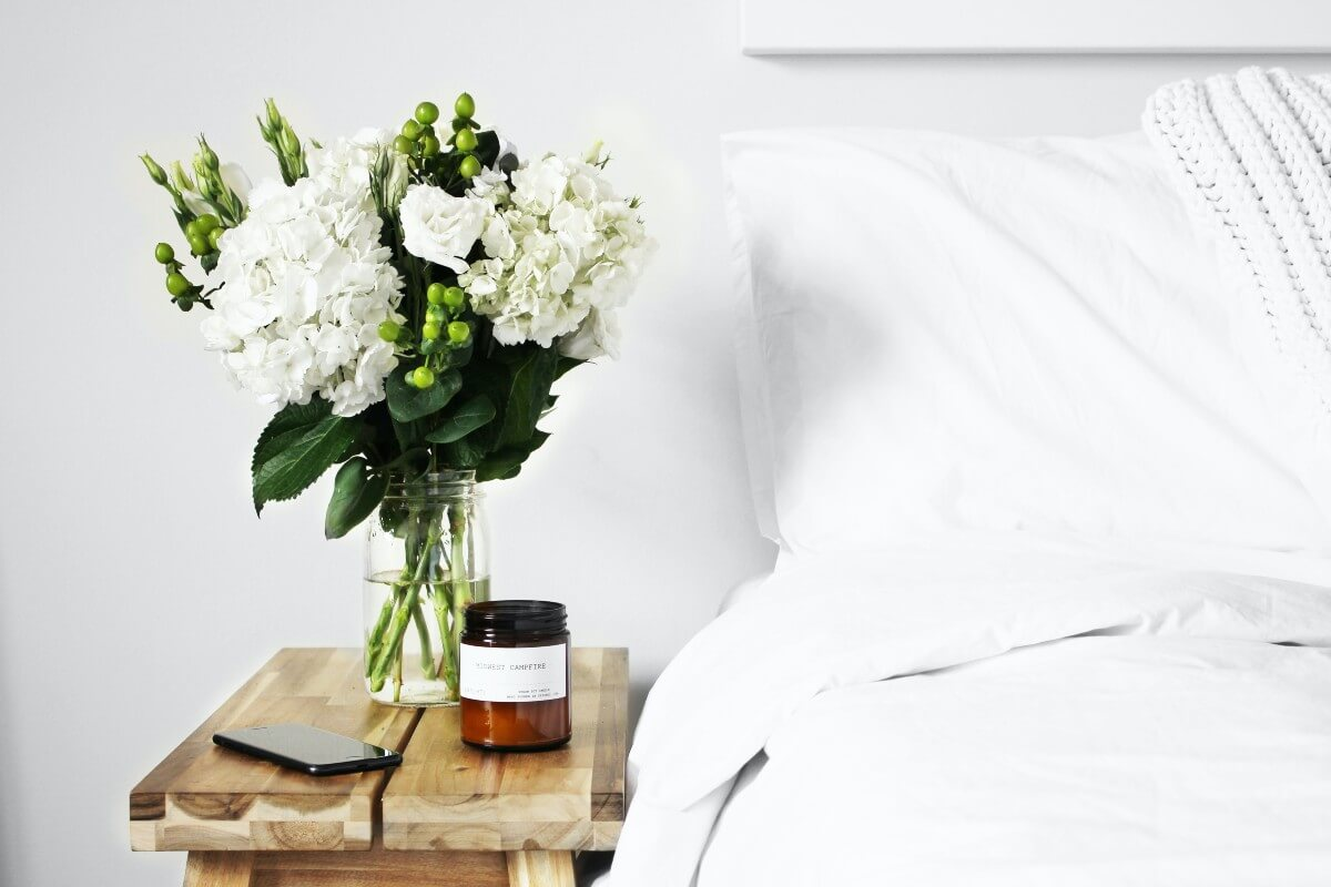 Vase of white flowers and a candle on a wooden nightstand