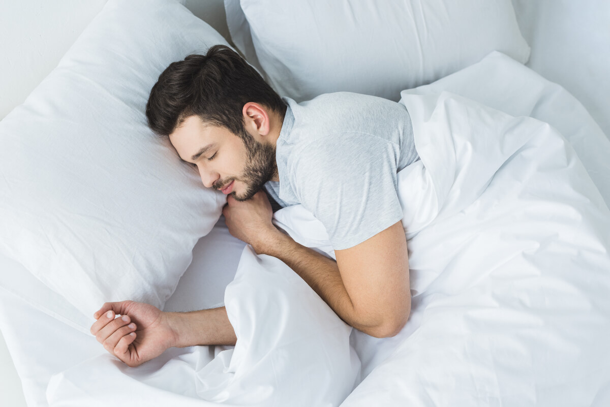 Man asleep in a bed with cozy, white bedding