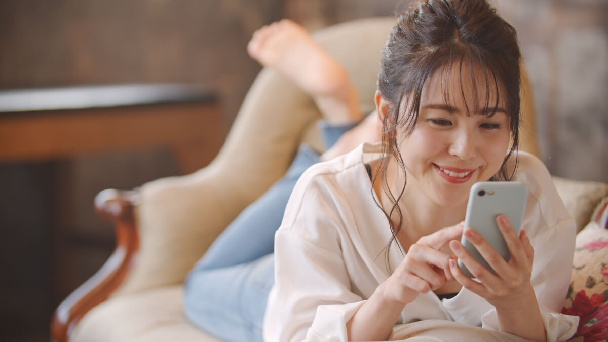 Woman smiling and using her smartphone to navigate financial milestones