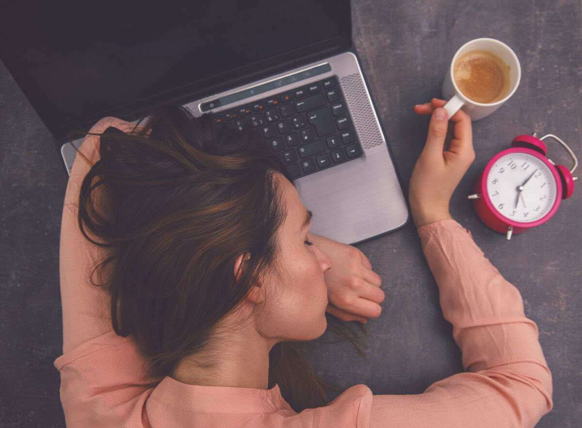 Woman asleep on her laptop holding a cup of coffee