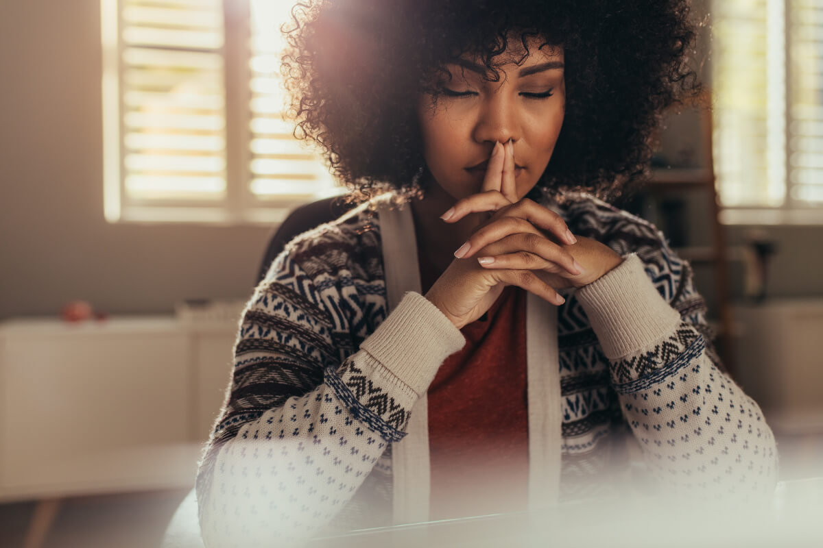 Woman sitting with her eyes closed practicing mindfulness