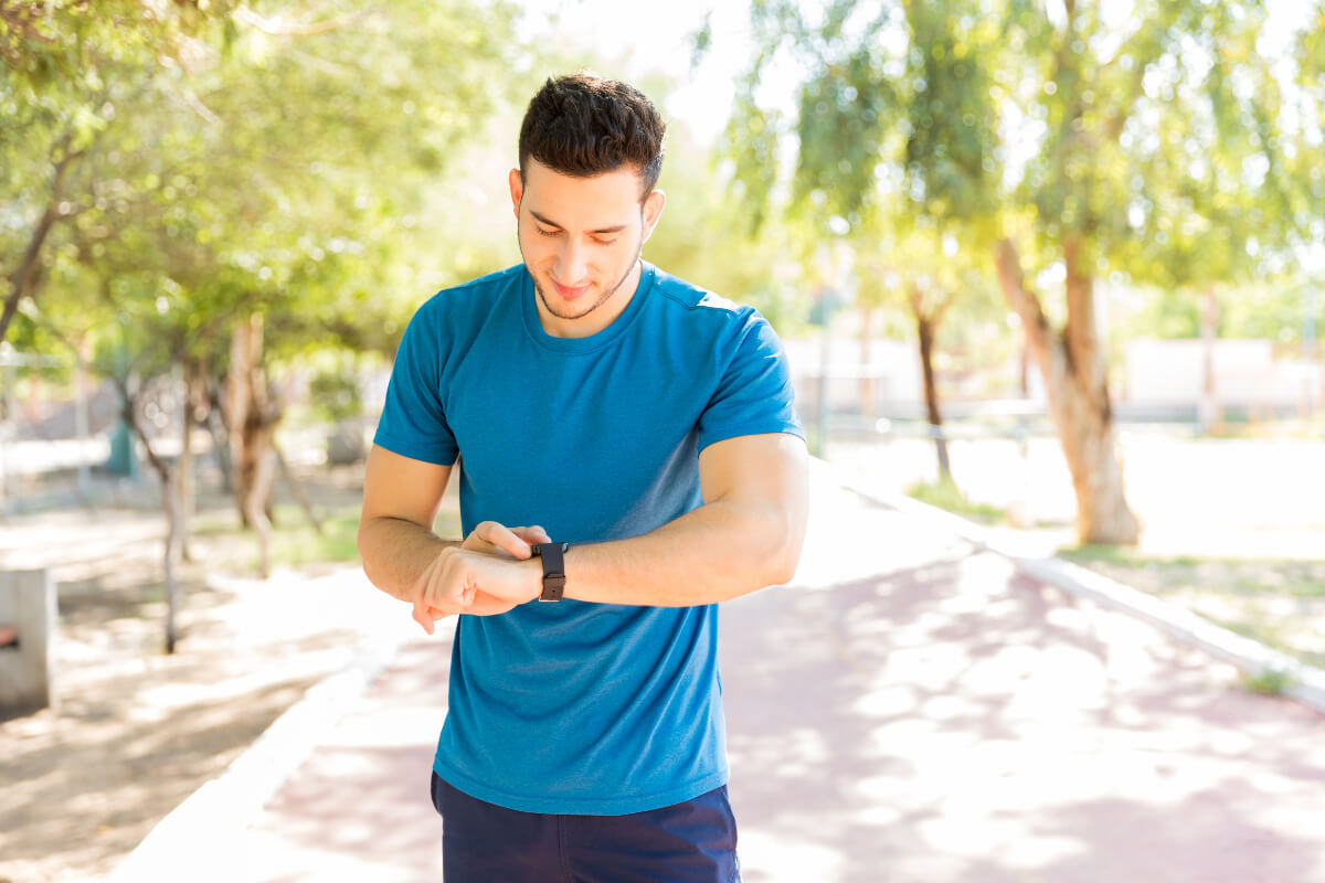 Man checking his step count on a tracker while jogging down a tree-lined path