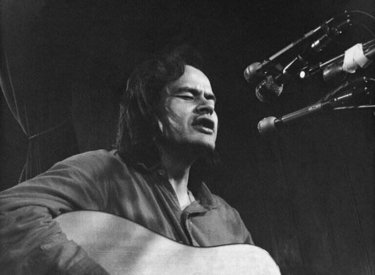 Black and white photo of Willie Dunn singing and playing guitar, 1976