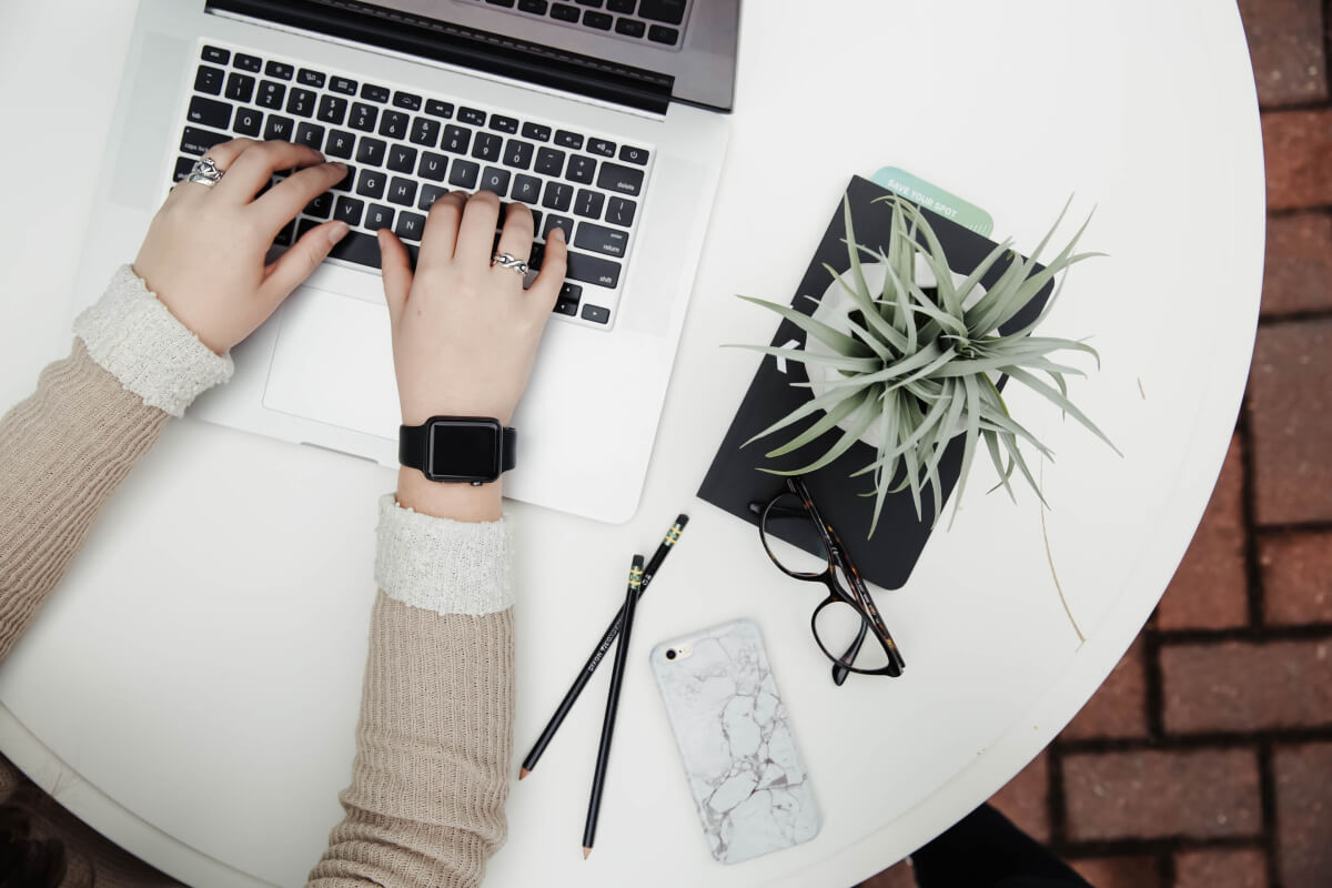 person's arms working on laptop beside a plant on a white table
