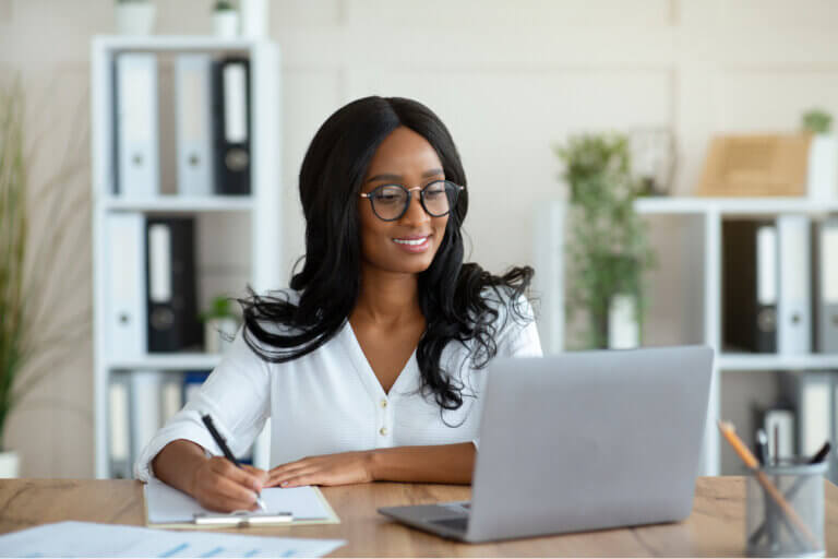 Woman sitting at the computer working on her financial milestones