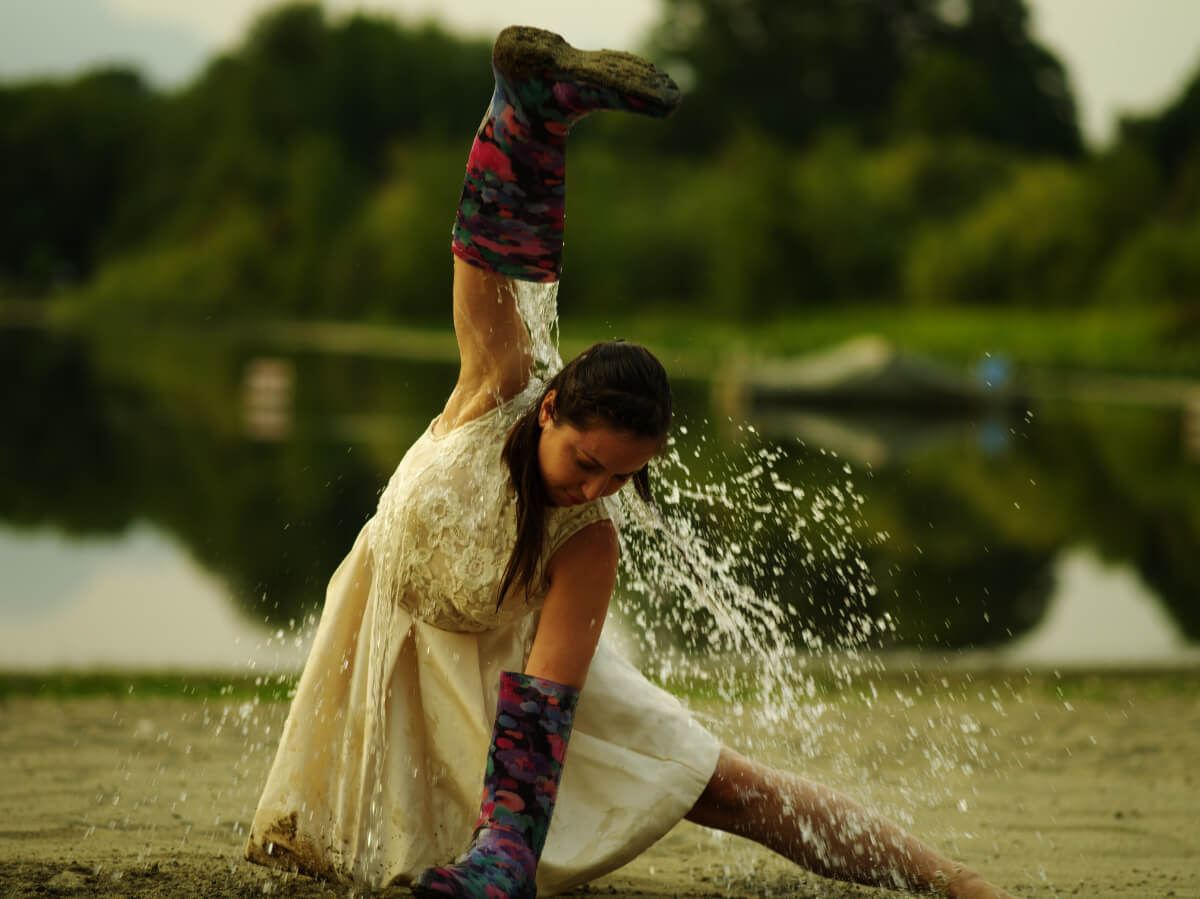 woman dancing out side in rain as part of immersive theatre production