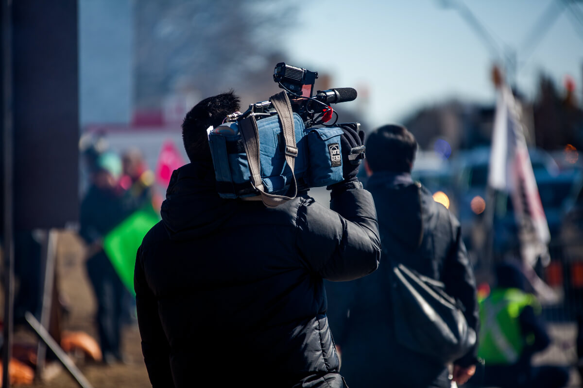 man holding a movie camera to document Indigenous Peoples' Day 2021