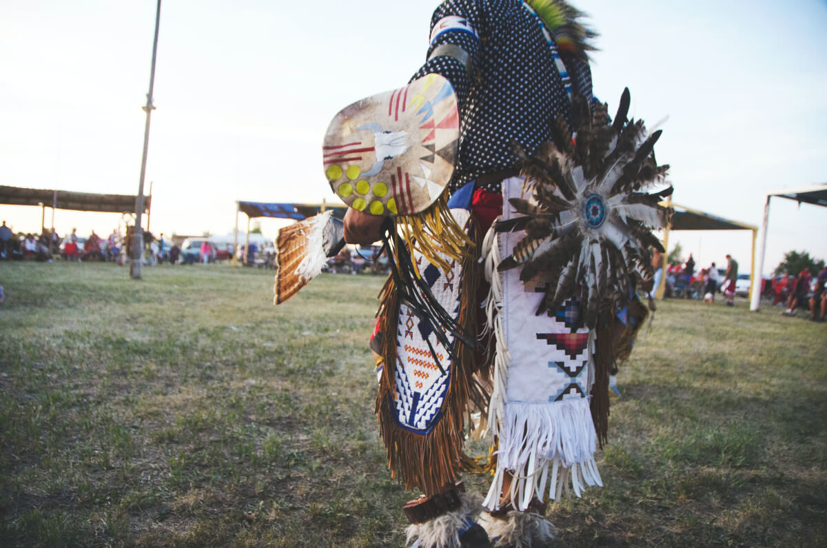 an indigenous person dressed in traditional attire at a pow wow celebrating Indigenous Peoples' Day 2021