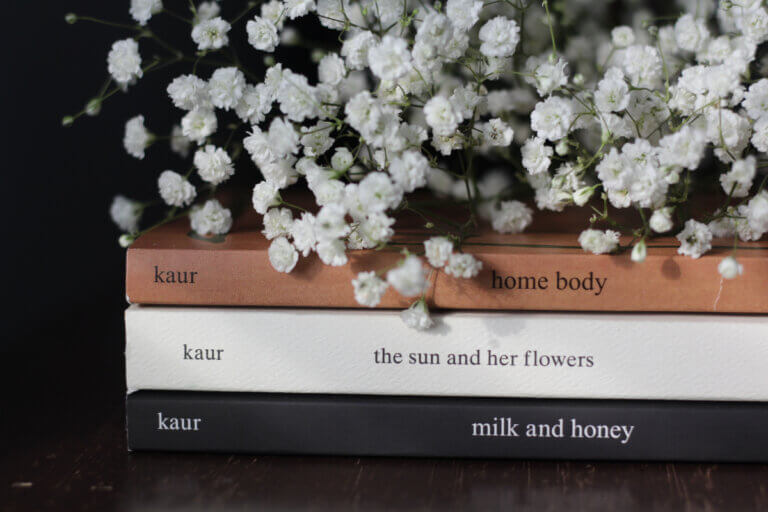 Stack of books by Instapoet Rupi Kaur topped with a bundle of white flowers