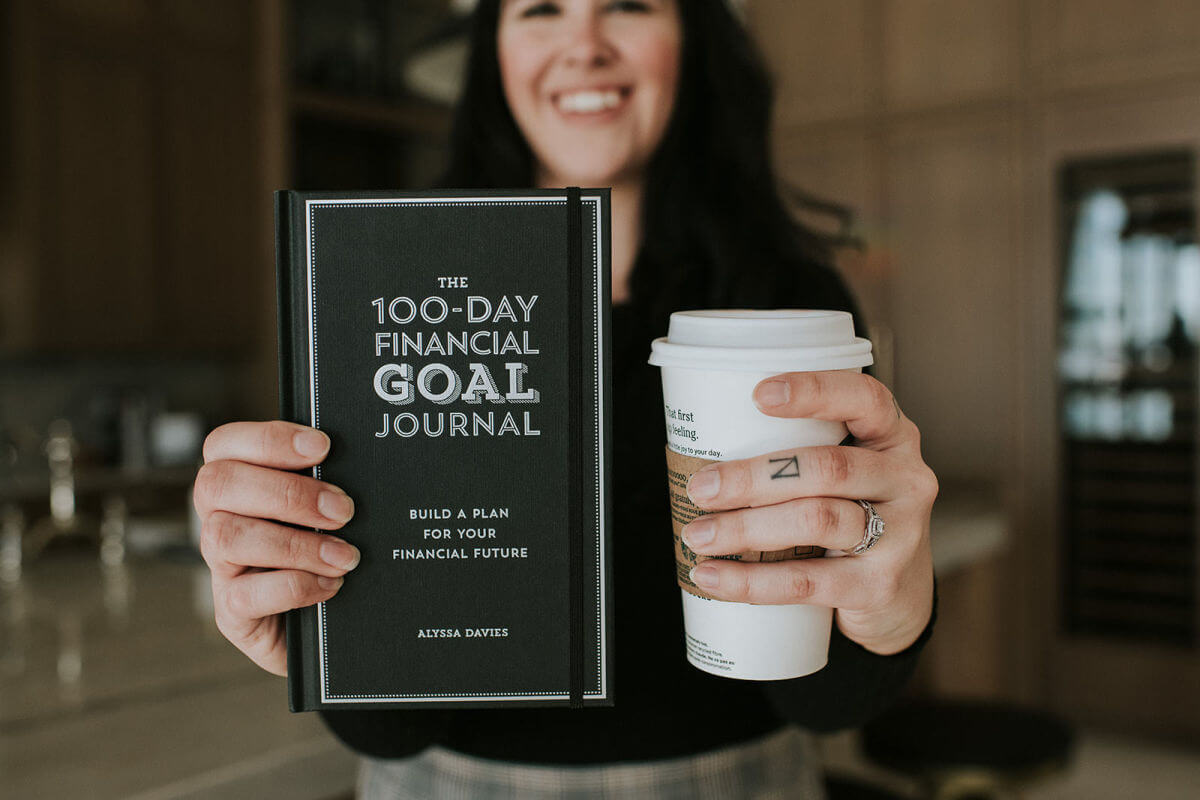 woman holding up financial goal journal to help with investing