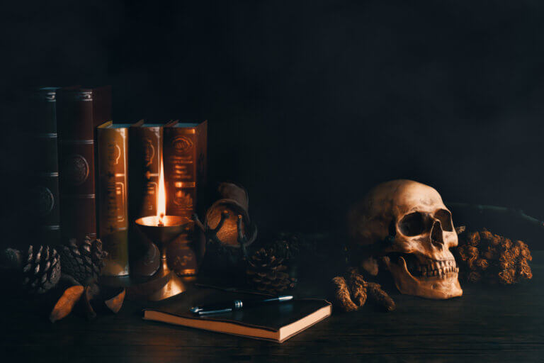 Scary, dark setting with books, candles, and a skull